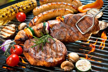 verschiedenes Grillfleisch und Gemüse auf einem Grillrost über glühenden Kohlen